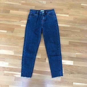 Mörkblå jeans med en snygg stentvätt. Snygga slitningar vid ankeln. Mom jeans, alltså en lite lösare fit. Använd endast en gång. Frakt tillkommer.