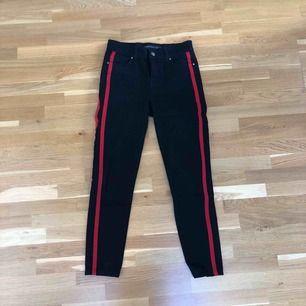 Svarta jeans med två röda streck på varje ben längs med sidorna. Högmidjade. Mom fit modell. Använd endast enstaka gång, som nya. Fint skick. Frakt tillkommer