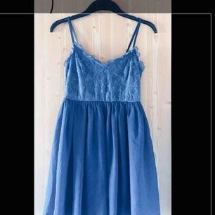 Väldigt söt blå klänning med glänsande spetsdetaljer upptill och justerbara axelband. Passar både till fest och vardag.