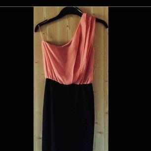 Svart och rosa klänning med räfflade detaljer och snyggt åtsittande nedtill.