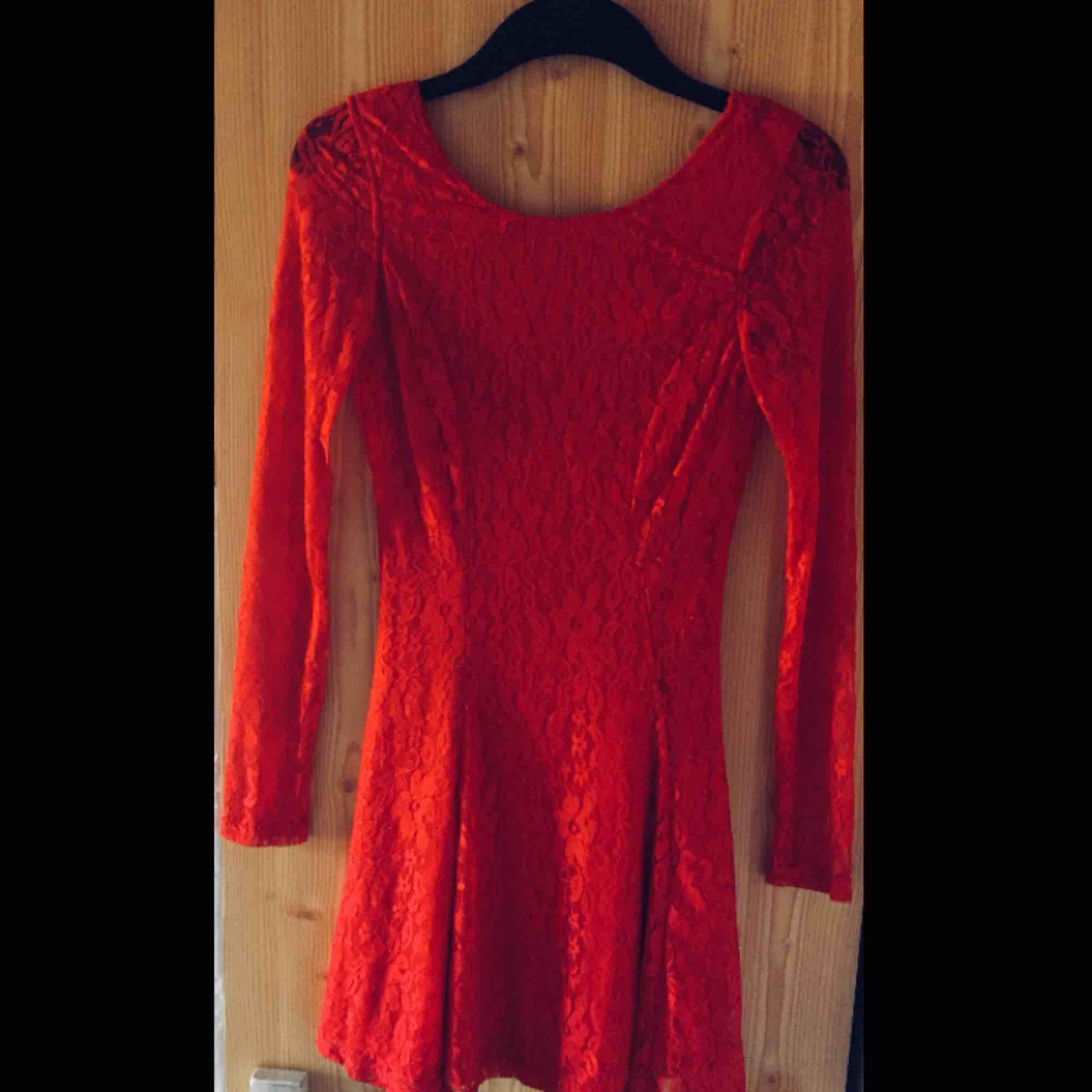 a47d67960026 Oanvänd röd spetsklänning med öppen rygg. Sitter åt i midjan och går ut  nedtill.