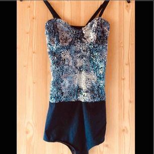 Tight och snyggt glittrande body med mörkblått genomskinligt tyg bak. Axelbanden är justerbara och avtagbara.