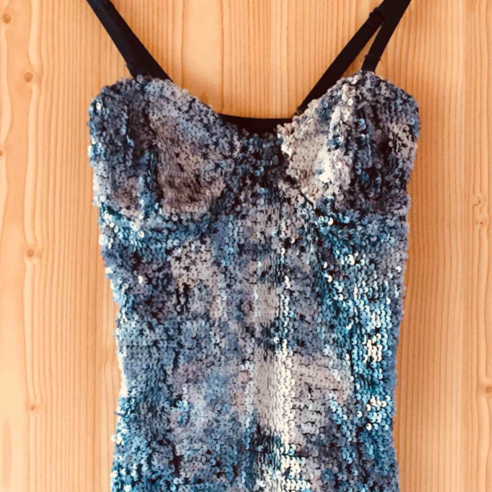 Tight och snyggt glittrande body med mörkblått genomskinligt tyg bak. Axelbanden är justerbara och avtagbara.. Toppar.