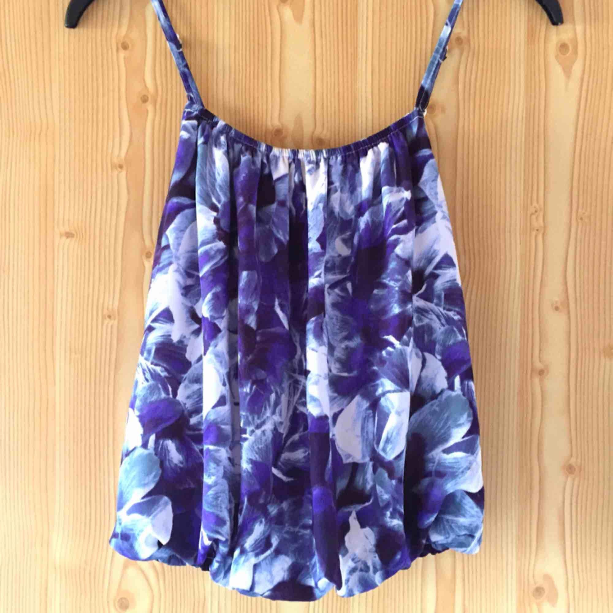 Superfin blå och vit blommig topp. Justerbara axelband och resår både upp och nedtill. Ett måste till sommaren!. Toppar.
