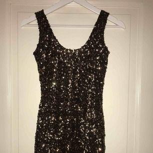 En superfin glittrig klänning perfekt till nyår, svart inne tyg så den inte ska klia osv. Använd endast 1 gång så den är i bra skick. Köptes från bik Bok (köparen står för frakten)