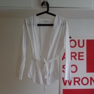 Vit omlottskjorta från Mango. Vitt knytbälte i midjan och lite oversize i storleken. Knappt använd.