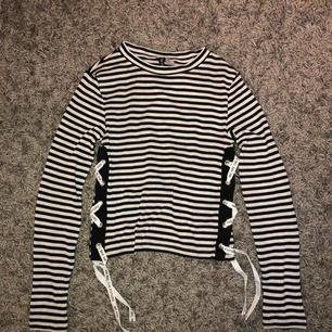 Svart/vit randig tröja med snörnings detalj nedtill. Passar mig som är XS 😊 Köparen står för frakten!