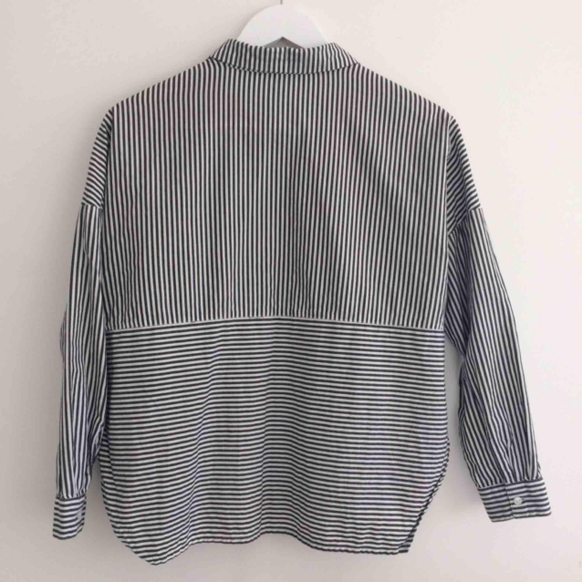 Grå/vit-randig skjorta med slitsar i sidorna. Från Monki, toppenskick! Frakt 40kr. Skjortor.