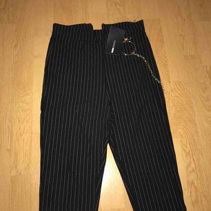 Helt ny och oanvänd högmidjade byxor/leggins. Kedja i detalj. Svart och vita linjer. Storlek S