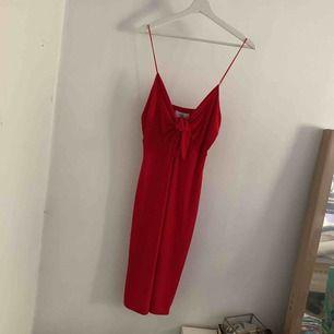 En figurnära klänning i röd från Rebecca Stella.