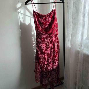 Supersöt röd klänning med rosa blommor på! I väldigt fint skick, frakten ingår!