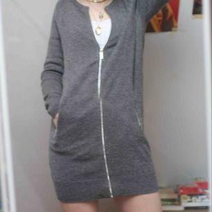 En lång kofta som kan användas som klänning eller kofta, dragkedja fram och vid fickorna. Köpt på JC för 400kr