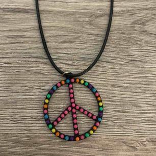 Coolt halsband med fredsmärke på läderband. Lite av en hippe-style.