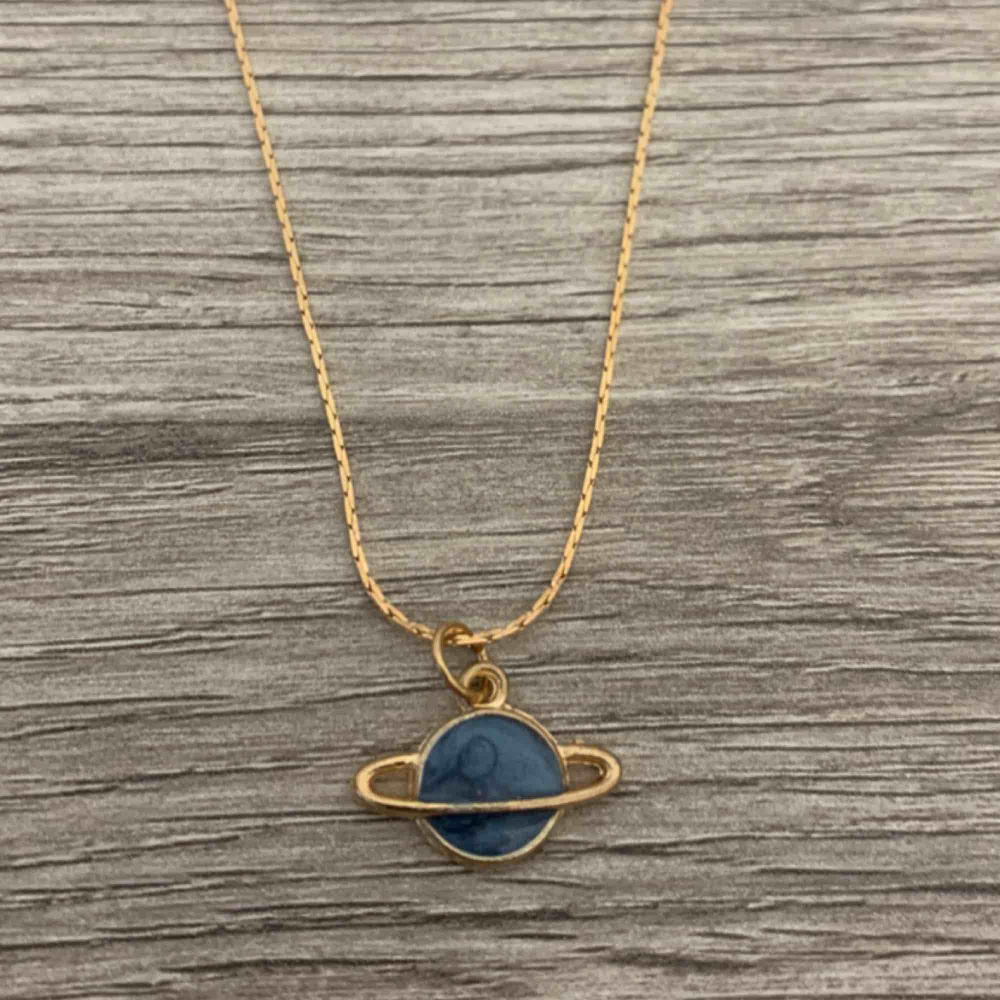 Fin guldig kedja med Saturnus i blå sten som berlock. . Accessoarer.