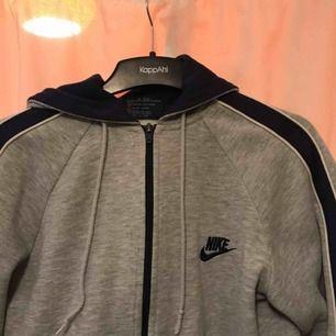 Grå Nike-hoodie med mörkblå detaljer. I fint skick! Kan mötas upp men också frakta