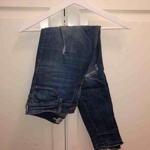 Blåa jeans med slitningar från lager 157. Små hål på båda sidorna av låren. 30kr + frakt
