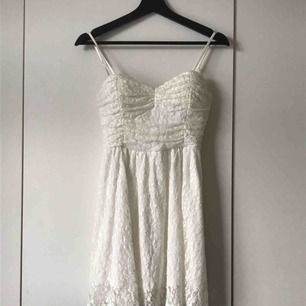 En jättefin, vit spetsklänning. Jag har köpt den begagnad och sedan använt den en gång på min student, så den är i använt skick. Lappen är tyvärr bortklippt men klänningen passar mig som har XS/34. Axelbanden är avtagbara. Kan skickas mot fraktkostnad.