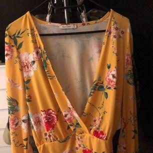 En fin gul blommig body från Nelly i storlek S, använd få tal gånger och super bra skick. Den har hål i armarna, svårt att förklara men super fint på! + Frakt