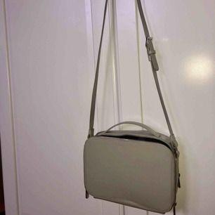Beige/grå väska från &other stories med detaljer i silver! Har två olika stora fack och även mindre inuti.