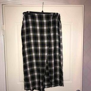 Rutig kjol med knappat och slits. Pris inkl frakt