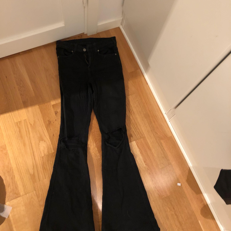 Svarta flare jeans från dr denim med hål på knäna. Jeans & Byxor.
