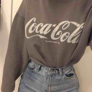 Beige Coca Cola sweatshirt inköpt från Bikbok. Storlek XS men passar betydligt bättre som S vilket jag vanligtvis brukar ha, trots det sitter den löst på mig. Sparsamt skick, använd max 10 gånger. Nypris 300kr säljes för 100kr