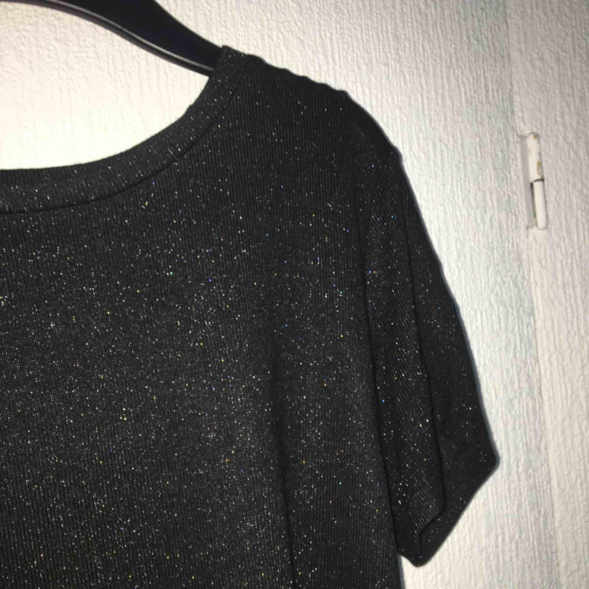 Glittrig svart t-shirt, endast använd en gång.  Betalas med swish, köparen står för frakt. . T-shirts.