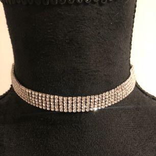 Halsband i chokermodell med strass från Glitter. Skickas mot fraktkostnad 20kr.