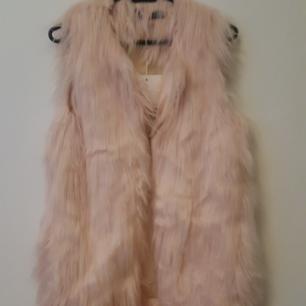 Fin rosa pälsväst i 32, oanvänd med tag kvar. Betalning via swish  Köparen står för frakt