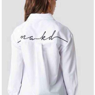 Vit lite oversize skjorta från NA-KD men logo på ryggen. Använd 1 gång