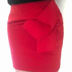 Färg: röd.  Strl: xs.   Snygg kjol från zara. Detalj av en knut/rosett framtill. Sluts igen med dold dragkedja bak. Stretch material. OBS. Aldrig använd. Dvs fint skick. Fraktkostnad tillkommer, betalning via swish.