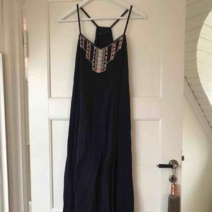 En fin mörkblå långklänning med pärlor på bröstet från Zara