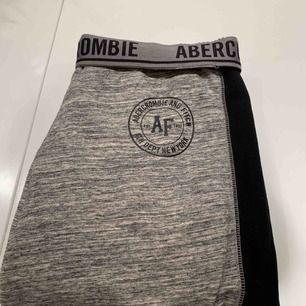 Abercrombie & Fitch-mjukisbyxor. Gråa med svarta sidor samt muddar längst ned ❣️✨   Priset inkluderar ej frakt.
