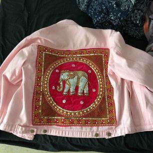 Rosa Jeans Jacka från Elsie and Fred, väldigt unika designers från Uk.  På baksidan är det en handgjord orientalisk motiv med en elefant på.   Använd bara en gång så den är helt ny.  Storlek M/L