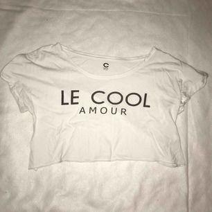 En vit kroppad t-shirt med svart text. Använd 1 gång kanske. Säljes pga. för liten storlek❤️