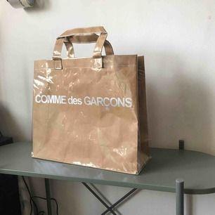 Äkta Comme des garcons tote bag I papper täckt utav PVC plast. Nypris 1299 kr. Bra skick.   563 kr med Spårbar frakt.  Rabatt vid snabb affär.  Mvh