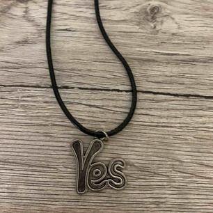 Coolt halsband med med hänge i form av yes. Silverfärgad hänge på svart läderband.