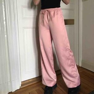 Sååååå fina rosa satinbyxor från Missguided, använda ett fåtal gånger men dom är som nya! Säljer pga inte min stil längre. Jag har sytt upp dom så det går att sprätta upp och få dem längre, jag är 170cm. Möts upp eller fraktar, köpren betalar frakt 💖💖💖