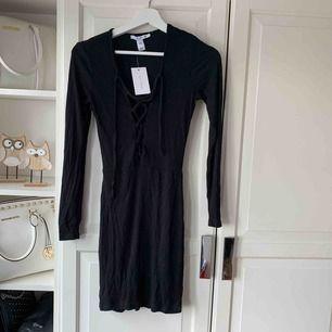 Säljer en oanvända svart klänning med knyten över bröstet. Superfin och oanvänd!
