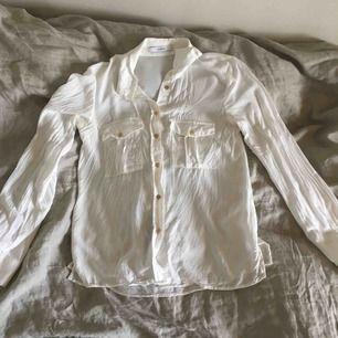 Skjorta i tunt material med guld knappar
