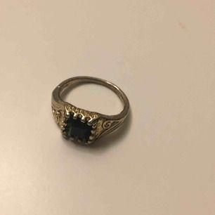 Guldfärgad ring med liten svart sten. Möts i Örebro eller skickar, köparen står för frakt