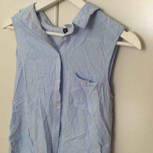 Ännu en sak från H&M! I storlek 42, skulle säga att den passar en M/L. Har en ficka på framsidan och inga ärmar. Är blå och vit randig. Aldrig använd, perfekt för sommaren :).