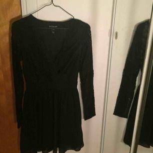"""En jättesnygg svart klänning från Wilma Holmqvists kollektion """"Hickap"""" men spets ner till och schyffon ner till. Dragkejda i sidan och band i midjan. Går lite över knäna."""