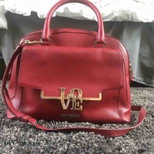 Stor Love moschino handväska i röd läderimitation med guld detaljer, kommer med dust bag  Lätt utsliten på två ställen men annars i fint sick  Skriv om ni har några frågor, diskutera priset eller vill ha mer bilder 😊
