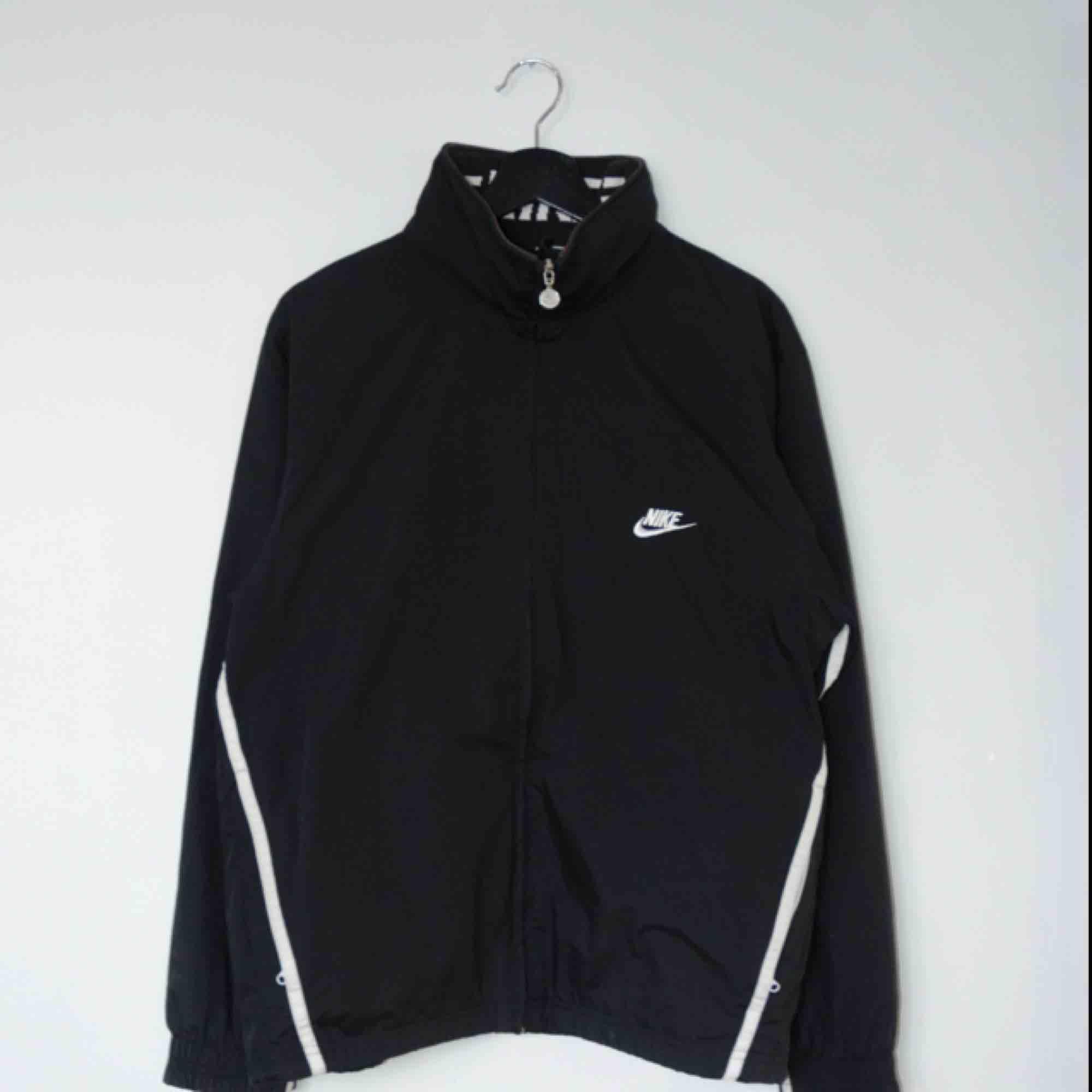 Säljer en vintage svart Nike trackjacket/windbreaker! Den har en ihopfällbar luva och en insida i mesh!  Size: Medium Cond: 8/10 (gott skick). Jackor.