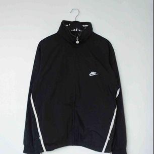 Säljer en vintage svart Nike trackjacket/windbreaker! Den har en ihopfällbar luva och en insida i mesh!  Size: Medium Cond: 8/10 (gott skick)