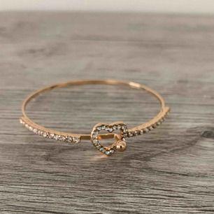 Fint armband i guldfärg med hjärta i strass!