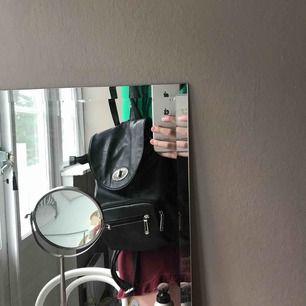 En lagom stor ryggsäck i fakeskinn med reglerbara band, många fack och rymlig insida. Vet ej vart jag köpt den tyvärr.