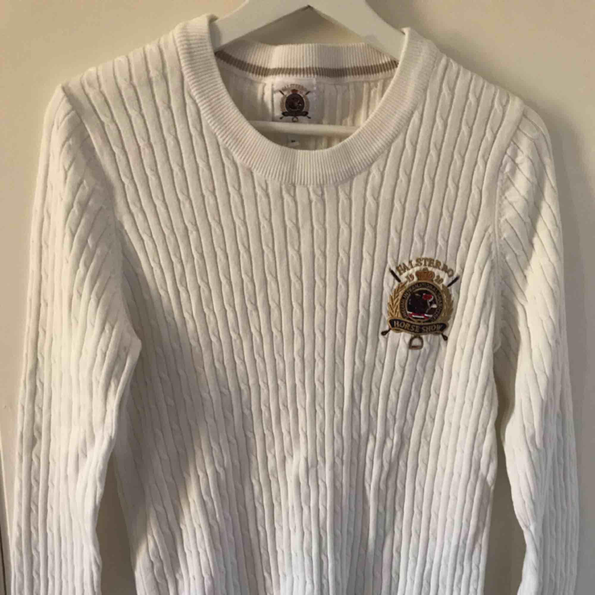 Vit kabelstickad tröja med tryck Står XL, men extremt liten i storlek, mer som M eller L Aldrig använd. Tröjor & Koftor.