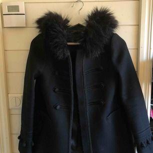 Svart kappa med luva och svart päls från Zara. Kortare i modellen men väldigt fin på vintern. Försluts med knappar som finns längs med kappan. Köparen står för frakten!